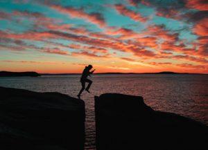 Mann springt über Abgrund.